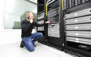 It engineer or technician monitors and solving problems with blade servers in data rack. Calling technical support about hardware problems in datacenter.