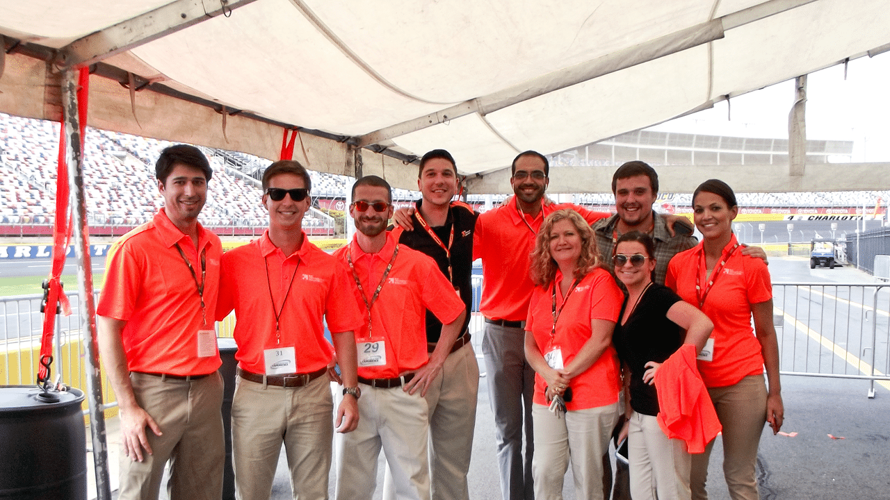 Employees at Biz Technology Solutions standing together at Nascar event