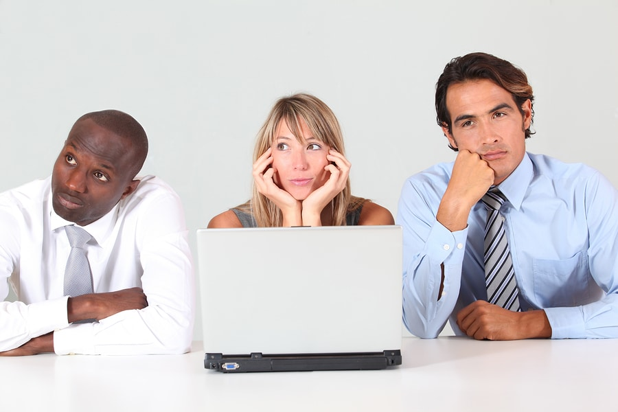 Business team with bored look in front of laptop computer