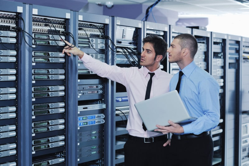 Group of young IT engineers in network server room solving problems, giving help and support