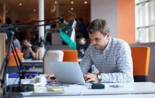 Software developer working on computer at modern office