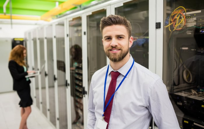 Smiling technician standing in a server room