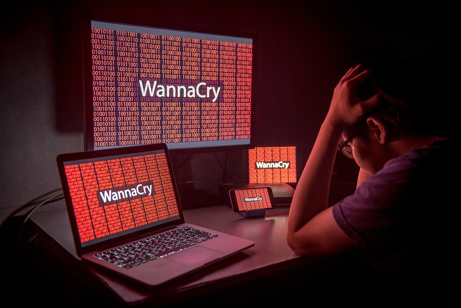 Young male frustrated and confused by WannaCry ransomware attack on desktop screen, notebook, and smartphone.